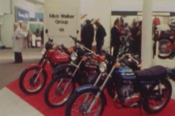 Image of a line of motorbikes on display at a trade show.