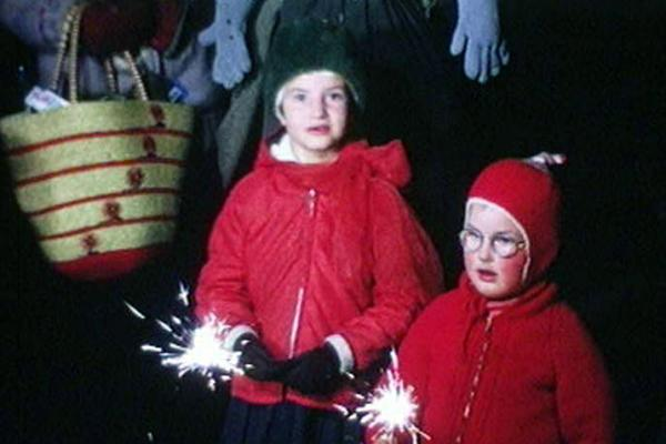 A colour still image from a 16mm home movie showing two children with sparklers in the early 1970s.