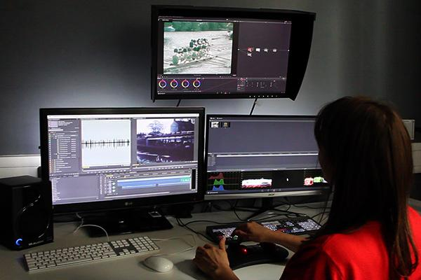 An image of MACE's grading suite: a rear view of the operator using three screens.