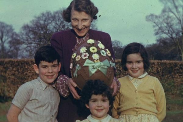 A colour still image from a home movie showing a family group with a huge Easter egg.