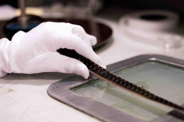 An image of 16mm combined magnetic film being inspected on a winding bench.