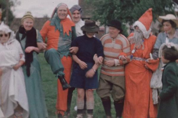 A colour still image from Coronation Festivities in Herefordshire (1953) showing a group of adults in fancy dress.