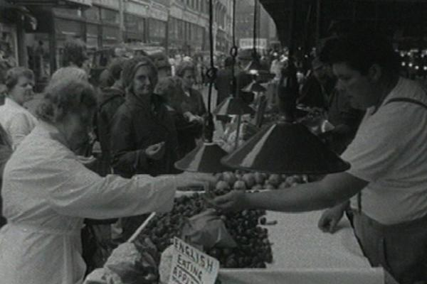 Black and white image of a green grocer serving a customer.