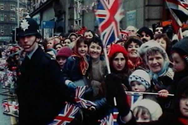 Image of a crowd waving Union Jacks, and a policeman standing by.