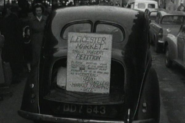 Black and white image of a car, with a placard reading Leicester market small traders petition.
