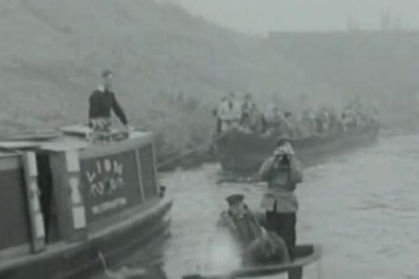 Black and white image of a canal boat pulling another boat.