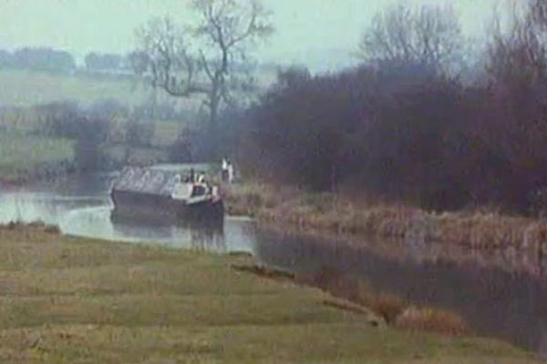 Image of a canal boat along the river.