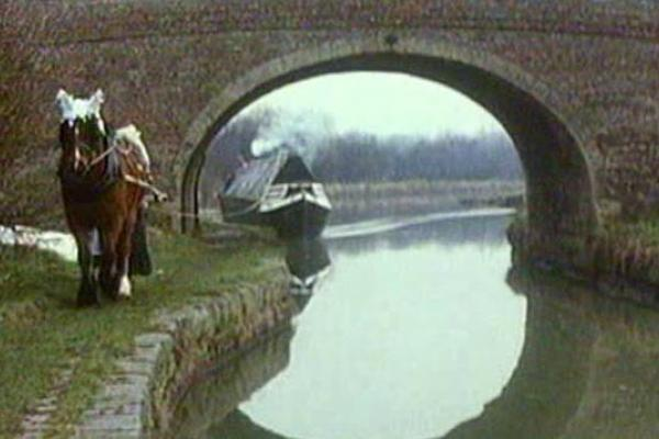 Image of a canal boat going under a small bridge.