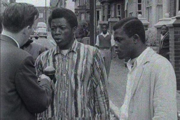A black and white still image from an ATV news report showing two black men being interviewed about the Dudley race riot of 1962.