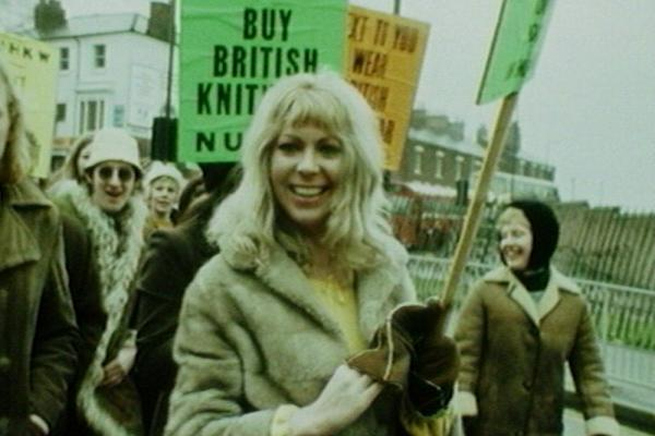 Image of a textile rally, along with placards and slogans.
