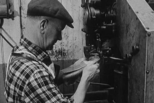 Black and white image of a worker making a shoe.