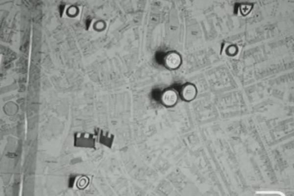 Black and white image of a map littered with pins.