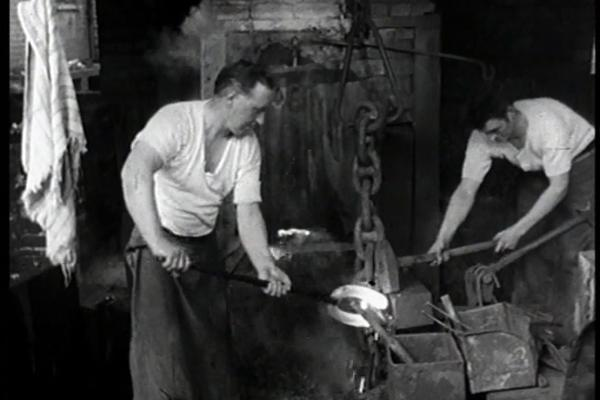 Black and White image of workers hammering hot iron.