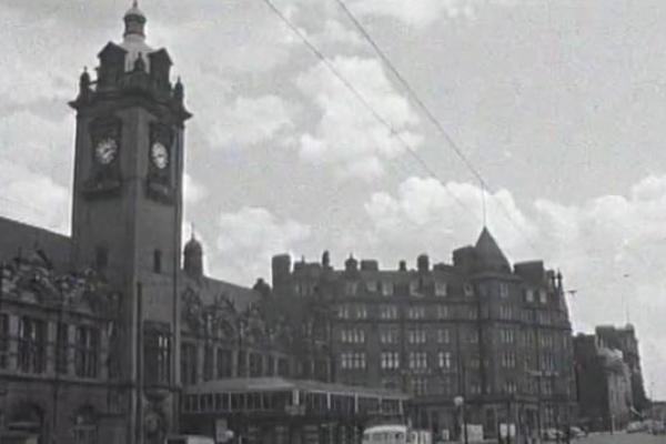 Black and white image of the exterior of a bus station.