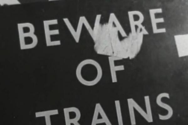 """Black and white image of a sign reading, """"Beware of Trains""""."""