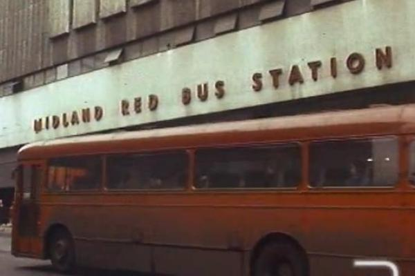 Image of a red bus leaving the midland red bus station.