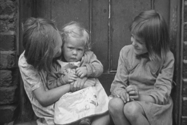 A black and white still image of two girls sitting on a doorstep holding a baby.