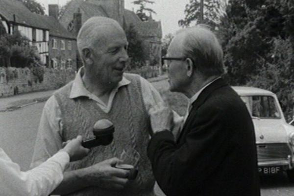 black and white image of a priest and fellow villager being interviewed.