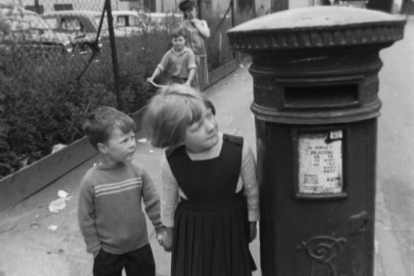 Still image from [Midlands News: 09.07.1963: Boy locked in pillarbox at Hockley]: a boy and a girl look up at a post box.